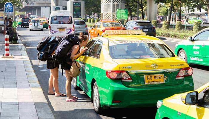 Routards discutant avec un chauffeur de taxi à Bangkok