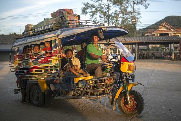 Un tuk-tuk emmène des voyageurs à la gare routière sud de Luang Prabang